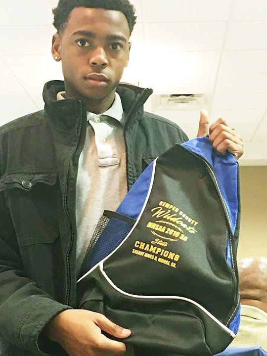 Young man in a black jacket holding Kemper County Wildcats backpack