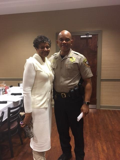 Sheriff standing with woman wearing white dress