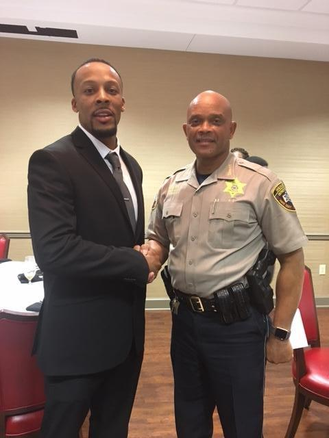 Man in suit shaking Sheriff's hand