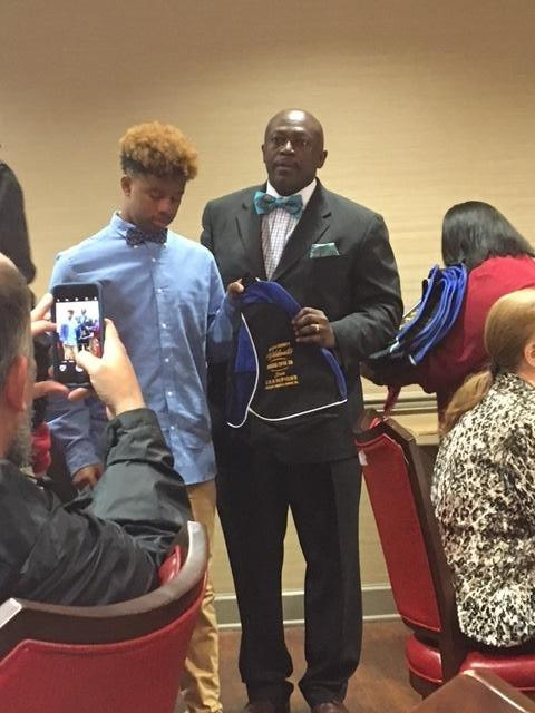 Man holding a Wildcats backpack, standing next to a young man in a bowtie